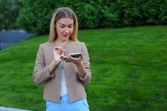 Bel écran de regard femelle de smartphone et sourires, supports Photo stock