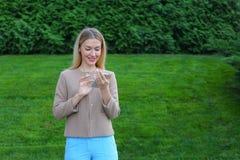 Bel écran de regard femelle de smartphone et sourires, supports Photographie stock