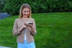 Bel écran de regard femelle de smartphone et sourires, supports Image stock