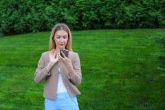 Bel écran de regard femelle de smartphone et sourires, supports Photographie stock libre de droits