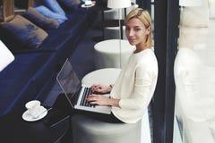 Bel étudiant avec un beau sourire et des cheveux courts et un pull blanc se reposant dans une barre à la mode avec l'ordinateur p Photographie stock libre de droits