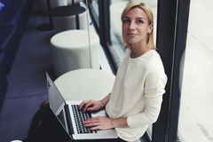 Bel étudiant avec un beau sourire et des cheveux courts et un pull blanc se reposant dans une barre à la mode avec l'ordinateur p Image stock