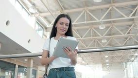 Bel étudiant de jeune femme à l'aide de son comprimé blanc dans le centre commercial, la vie heureuse d'université Photo stock