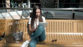 Bel étudiant de jeune femme à l'aide de son comprimé blanc dans le centre commercial, la vie heureuse d'université Image stock