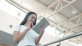 Bel étudiant de jeune femme à l'aide de son comprimé blanc dans le centre commercial, la vie heureuse d'université Images stock
