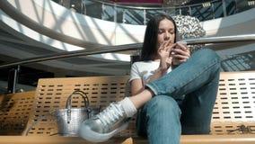 Bel étudiant de jeune femme à l'aide de son comprimé blanc dans le centre commercial, la vie heureuse d'université Photographie stock