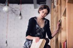 Bel étudiant féminin dans une bibliothèque Photo stock