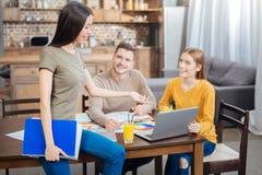 Bel étudiant regardant l'ordinateur portable tout en parlant à ses amis Photographie stock libre de droits