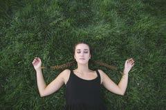 Bel adolescent de sommeil sur l'herbe Photographie stock