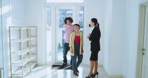 Bel agent immobilier la montrant à une nouvelle maison moderne à un jeune couple charismatique gesticulant avec des mains sourian banque de vidéos
