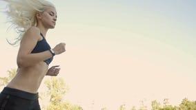 Bel ajustement et route blonde saine de femme allant avec le traqueur de forme physique banque de vidéos