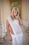 Bel ange blond avec des ailes de lumière blanche et la pose blanche de voile extérieures Photographie stock