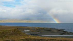 Bel arc-en-ciel au-dessus de fjord islandais en jour ensoleillé, bas nuages pluvieux et soleil banque de vidéos