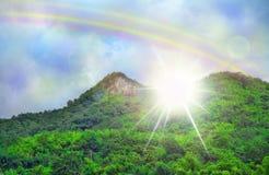 Bel arc-en-ciel de nuage de ciel, lumière dramatique de montagnes vertes Photo libre de droits