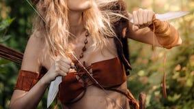 Bel archer de fille avec de longs cheveux blonds avec l'arc et l'arrowson un dos tenant deux bras froids de couteaux en acier photo stock