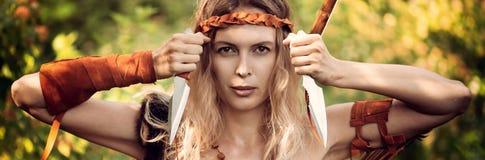Bel archer de fille avec de longs cheveux blonds avec l'arc et l'arrowson un dos tenant deux bras froids de couteaux en acier photos stock