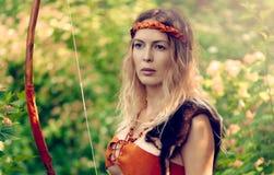 Bel archer de fille avec de longs cheveux blonds avec un tir à l'arc habillé en cuir image stock