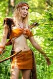 Bel archer de fille avec de longs cheveux blonds avec un tir à l'arc habillé en cuir photo libre de droits