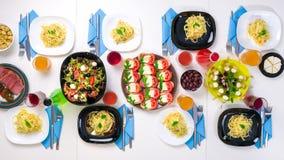 Bel arrangement de table avec des plats, des boissons et des parties de pâtes Image libre de droits