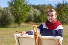 Bel artiste de fille peignant un beau tableau en nature Photos libres de droits