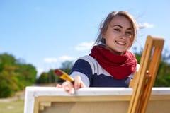 Bel artiste de fille peignant un beau tableau en nature Image stock