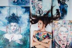 Bel artiste nu féminin entouré par la toile de peintures sur le fond de blanc de plancher balaye la palette image stock