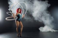 Bel artiste rouge féminin de cirque de cheveux tenant des cercles images stock