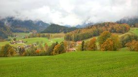 Bel automne scenary entre les champs verts et les arbres d'automne menant à une ferme sur un beau flanc de coteau images libres de droits