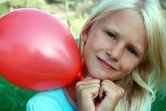 Bel emplacement blond de fille sur l'herbe et l'exploitation une boule rouge Photo stock