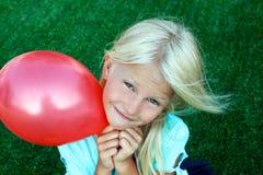 Bel emplacement blond de fille sur l'herbe et l'exploitation une boule rouge Images stock