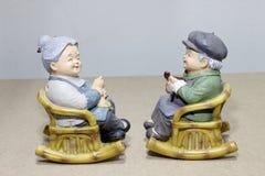 Bel emplacement de poupée de grand-parent basculant la chaise en bambou sur le fond en bois - la vie toujours Photographie stock libre de droits
