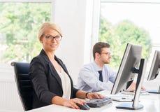 Bel employé de bureau féminin dans le formalwear avec le collègue sur le fond Photo stock