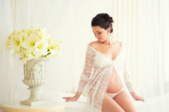 Bel enceinte dans le déshabillé blanc léger de dentelle dans la salle de bains Photo stock