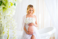 Bel enceinte dans le déshabillé blanc léger de dentelle dans la salle de bains Images stock
