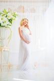 Bel enceinte dans le déshabillé blanc léger de dentelle dans la salle de bains Photographie stock libre de droits