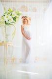 Bel enceinte dans le déshabillé blanc léger de dentelle dans la salle de bains Photos libres de droits