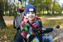 Bel enfant en bas âge sur un vélo en parc d'automne Photographie stock