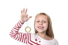 Bel enfant féminin doux avec des yeux bleus tenant les fournitures scolaires transparentes adhésives de bande Photographie stock libre de droits