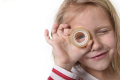 Bel enfant féminin doux avec des yeux bleus tenant les fournitures scolaires transparentes adhésives de bande Photos libres de droits
