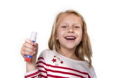 Bel enfant féminin doux tenant le concept de fournitures scolaires de bâton de colle Photo stock