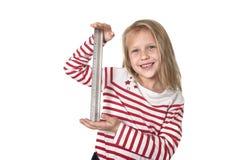 Bel enfant féminin doux tenant le concept de fournitures scolaires de règle Photos stock