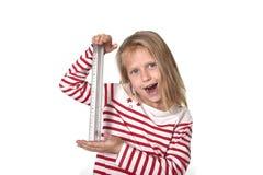 Bel enfant féminin doux tenant le concept de fournitures scolaires de règle Images libres de droits