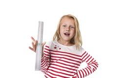 Bel enfant féminin doux tenant le concept de fournitures scolaires de règle Photo stock