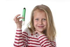 Bel enfant féminin doux tenant le dessin et le concept de fournitures scolaires de marqueur d'écriture Photo libre de droits
