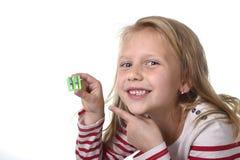 Bel enfant féminin doux avec des yeux bleus tenant des fournitures scolaires de taille-crayons de dessin Image stock