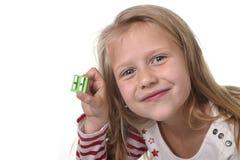 Bel enfant féminin doux avec des yeux bleus tenant des fournitures scolaires de taille-crayons de dessin Images stock