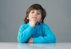 Bel enfant futé pensant sur le fond gris Images libres de droits