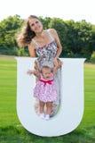Bel enfant heureux sur le plancher d'herbe avec la lettre Photo stock