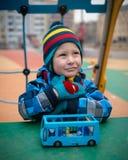 Bel enfant sur le secteur de terrain de jeu pendant l'hiver images stock