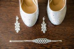 Bel ensemble d'accessoires de mariage, de chaussures blanches, de perle et de boucles d'oreille Photos libres de droits